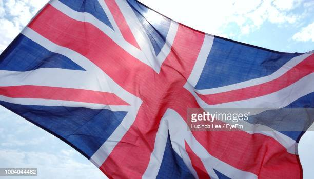 low angle view of british flag against sky - union jack stock photos and pictures