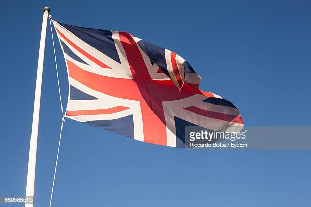 Low Angle View Of British Flag Waving Against Clear Blue Sky