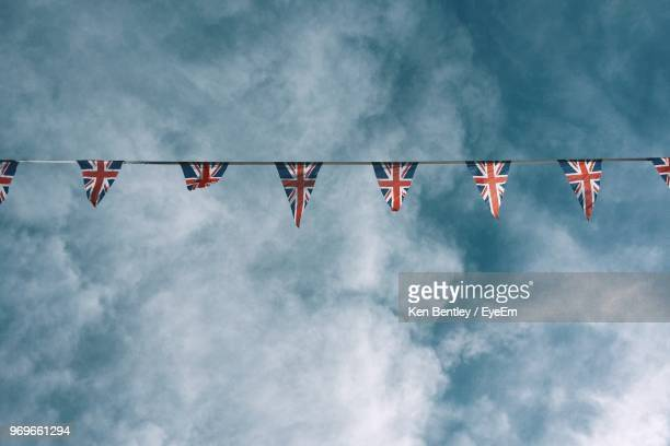 low angle view of british flags bunting against cloudy sky - bunting stock pictures, royalty-free photos & images