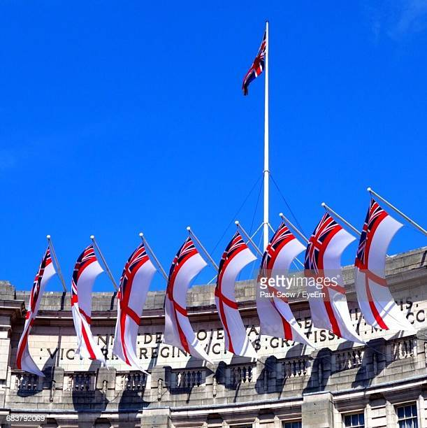 Low Angle View Of British Flags On Admiralty Arch Against Sky