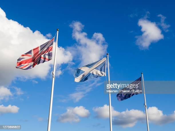 low angle view of british, scottish and european flags against blue sky - brexit stock pictures, royalty-free photos & images