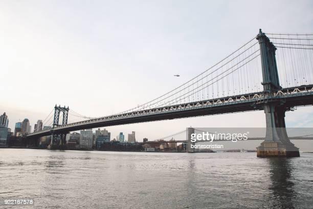 low angle view of brooklyn and manhattan bridge over river against sky - bortes imagens e fotografias de stock