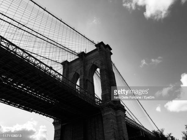 low angle view of brooklyn bridge against sky - brooklyn bridge stock pictures, royalty-free photos & images