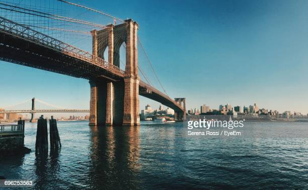 low angle view of brooklyn bridge over east river by city against blue sky - brooklyn bridge stock pictures, royalty-free photos & images