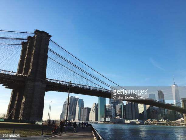 low angle view of brooklyn bridge over east river in city against blue sky - bortes stock pictures, royalty-free photos & images