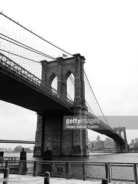 low angle view of brooklyn bridge over river against clear sky - brooklyn bridge stock pictures, royalty-free photos & images