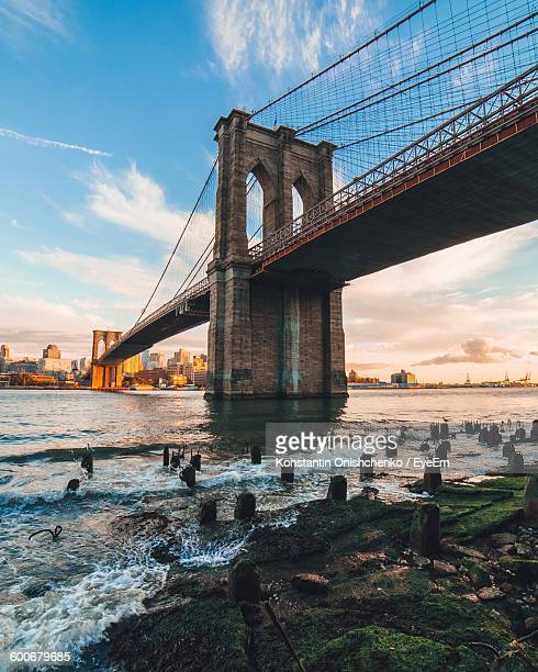 Low Angle View Of Brooklyn Bridge Over River Against Sky