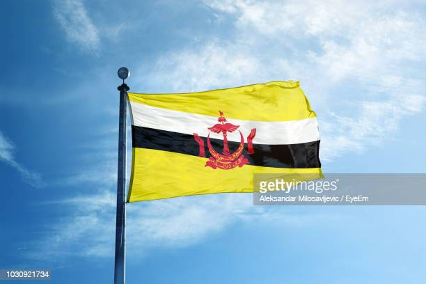 low angle view of brunei flag against blue sky - brunei stock pictures, royalty-free photos & images