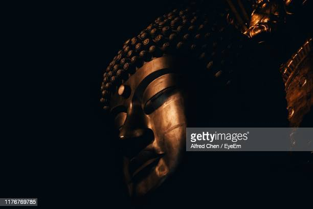 low angle view of buddha statue against black background - 仏陀 ストックフォトと画像