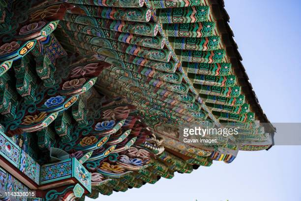 low angle view of buddhist temple roof against clear sky - korea stock pictures, royalty-free photos & images