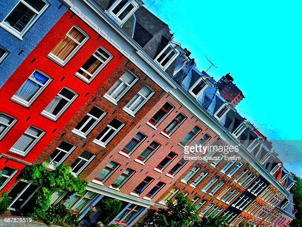 low angle view of building against blue sky - krausz stock-fotos und bilder