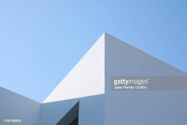 low angle view of building against clear blue sky - architecture stock pictures, royalty-free photos & images