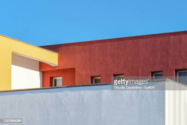 low angle view of building against clear blue sky - europa meridionale foto e immagini stock