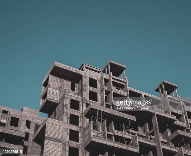 low angle view of building against clear blue sky - ナグプール ストックフォトと画像