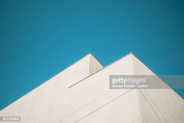low angle view of building against clear blue sky - high section stock pictures, royalty-free photos & images