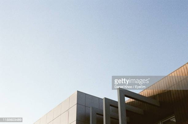 low angle view of building against clear sky - high section stock pictures, royalty-free photos & images