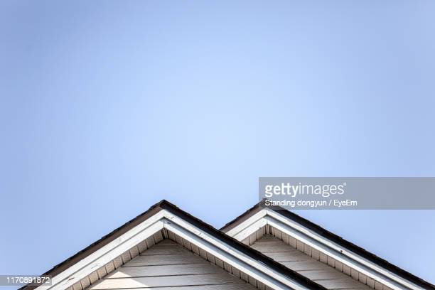 low angle view of building against clear sky - roof stock pictures, royalty-free photos & images