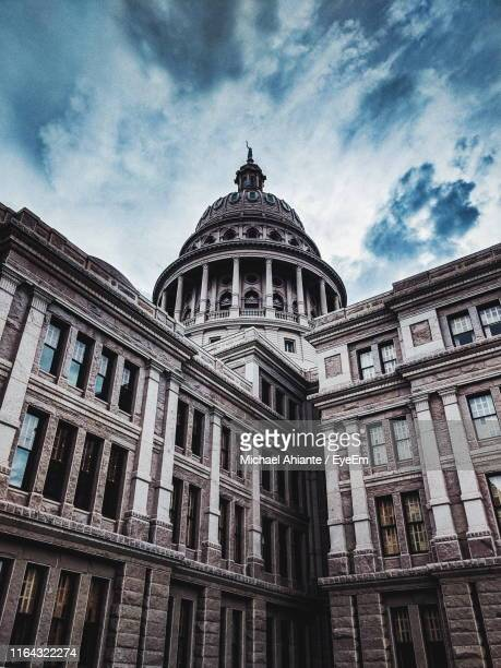 low angle view of building against cloudy sky - state capitol building stock pictures, royalty-free photos & images