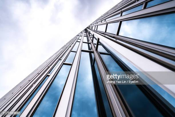 low angle view of building against cloudy sky - architectural feature stock pictures, royalty-free photos & images