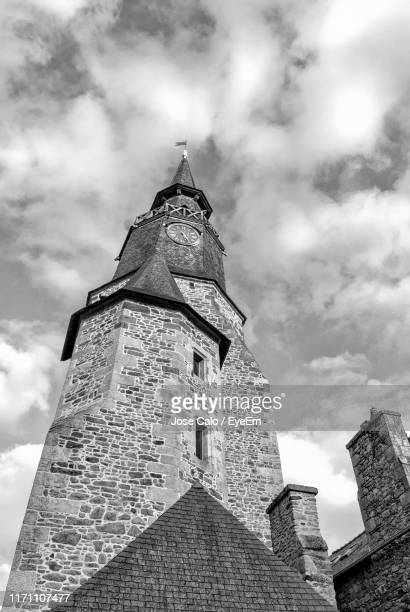 low angle view of building against cloudy sky - clock tower stock pictures, royalty-free photos & images