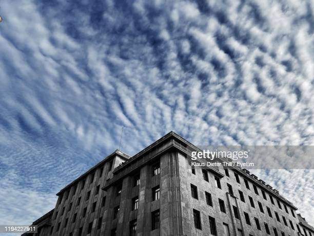 low angle view of building against cloudy sky - klaus-dieter thill stock-fotos und bilder
