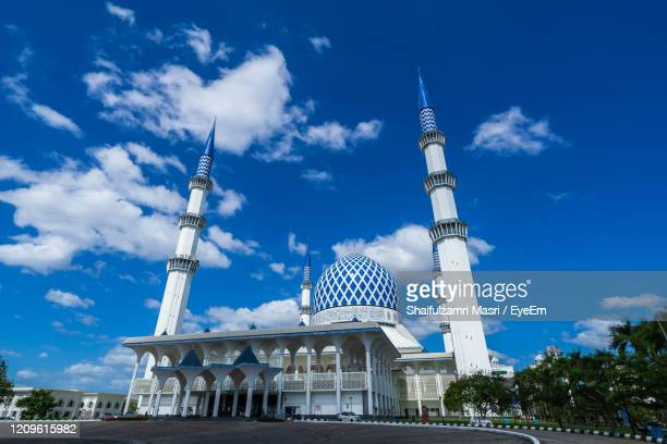 low angle view of building against cloudy sky - shaifulzamri stock pictures, royalty-free photos & images
