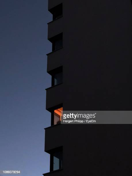 low angle view of building against sky at night - fensterfront stock-fotos und bilder