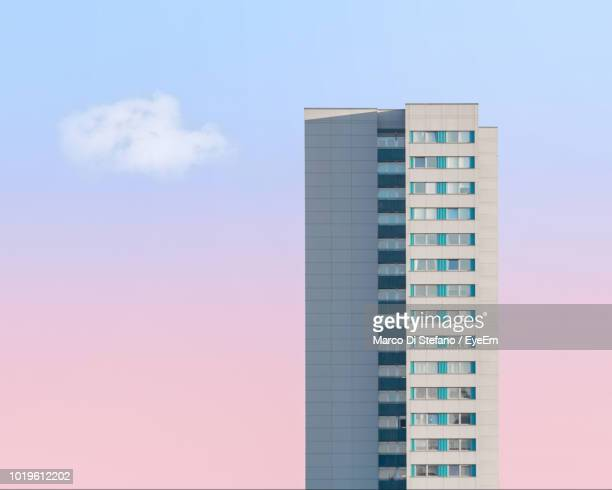 low angle view of building against sky - wolkenkratzer stock-fotos und bilder