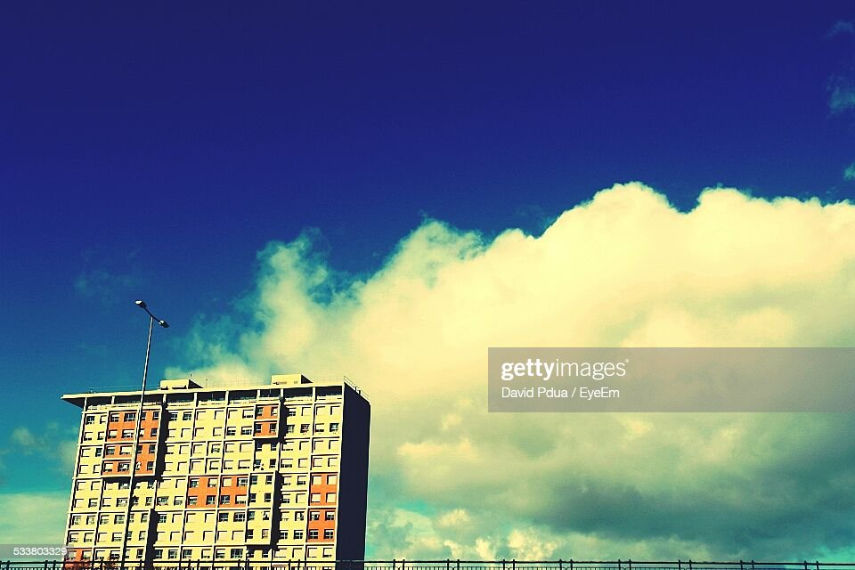 Low Angle View Of Building And Street Light Against Cloudy Sky : Foto stock