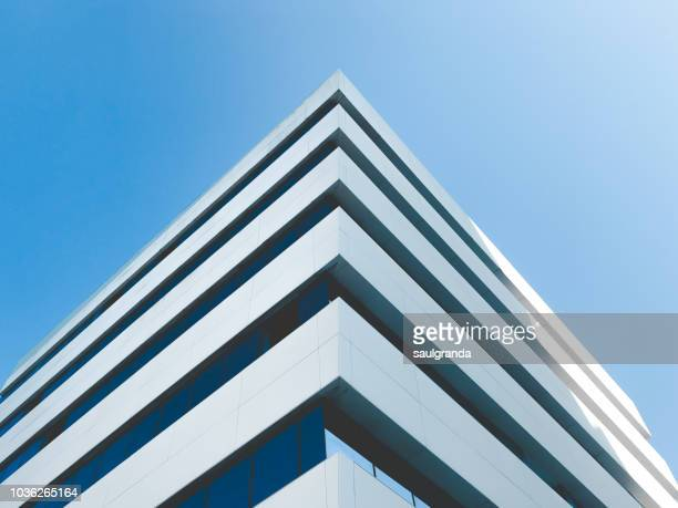 low angle view of building corner against clear blue sky - bürogebäude stock-fotos und bilder