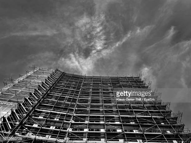 low angle view of building under construction against sky - klaus-dieter thill stock-fotos und bilder