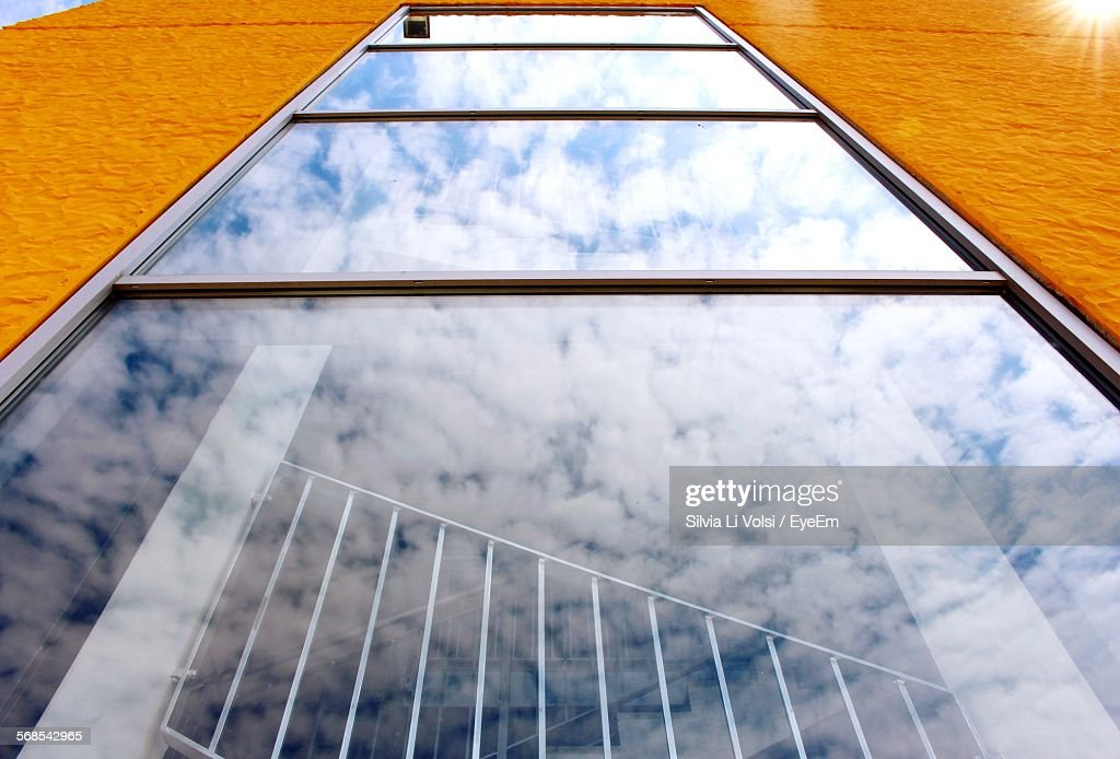Low Angle View Of Building Windows With Clouds Reflection : Stock Photo