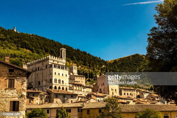 low angle view of buildings against blue sky - gubbio stock pictures, royalty-free photos & images
