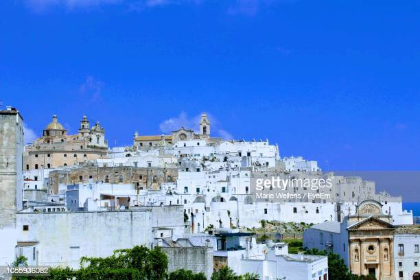 low angle view of buildings against blue sky - ostuni stock photos and pictures