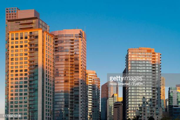 low angle view of buildings against blue sky - vancouver skyline stock pictures, royalty-free photos & images