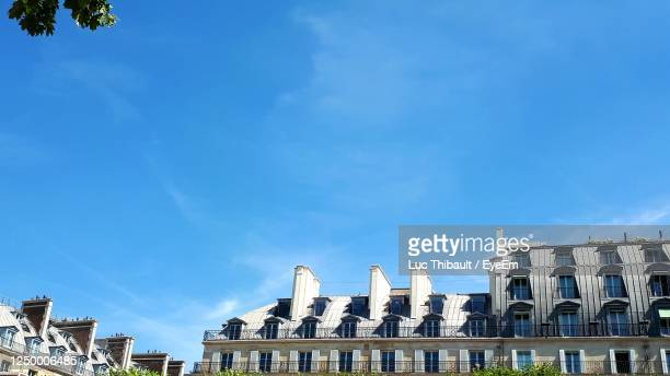 low angle view of buildings against blue sky - paris france stock pictures, royalty-free photos & images