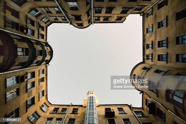 low angle view of buildings against clear sky - san pietroburgo russia foto e immagini stock