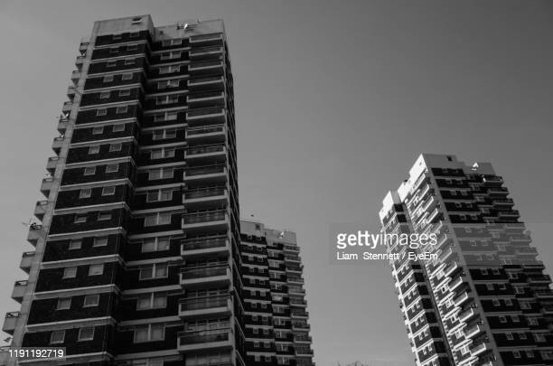 low angle view of buildings against clear sky - housing development stock pictures, royalty-free photos & images