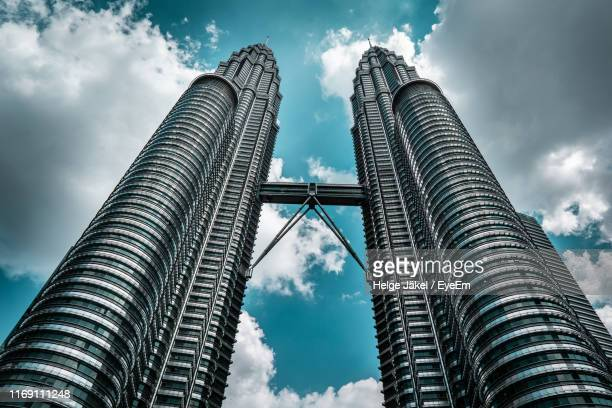 low angle view of buildings against cloudy sky - kuala lumpur stock pictures, royalty-free photos & images