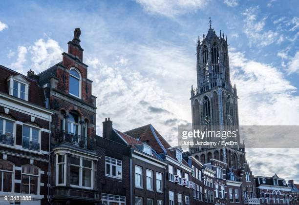 low angle view of buildings against cloudy sky - utrecht stockfoto's en -beelden