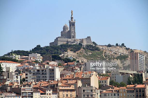 Low Angle View Of Buildings Against Notre-Dame De La Garde