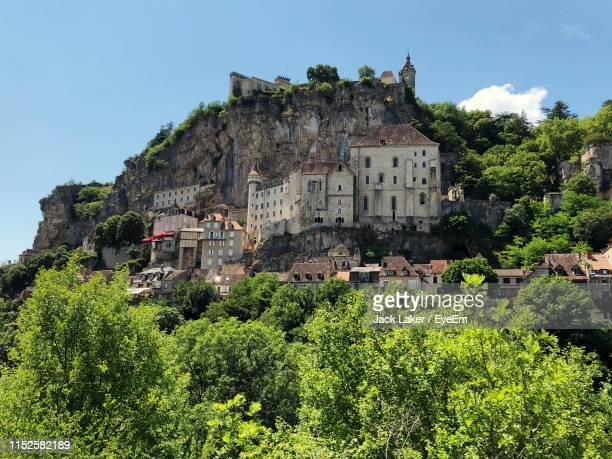 low angle view of buildings against rock formation - rocamadour stock pictures, royalty-free photos & images