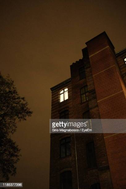low angle view of buildings against sky at sunset - fensterfront stock-fotos und bilder