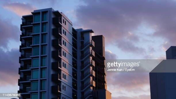 low angle view of buildings against sky during sunset - マンション ストックフォトと画像