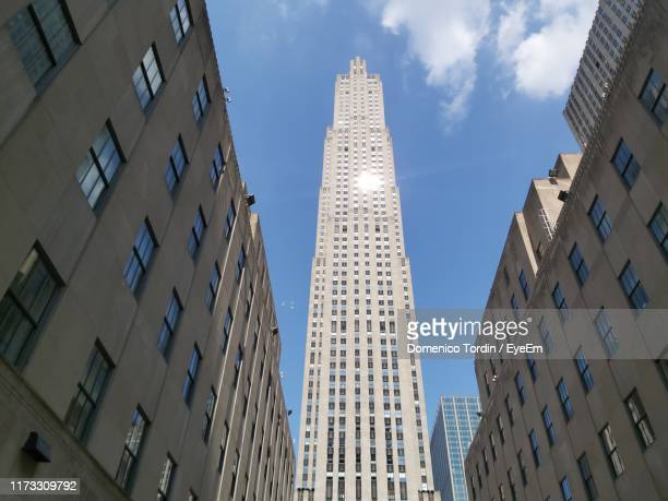 low angle view of buildings against sky - rockefeller center stock pictures, royalty-free photos & images