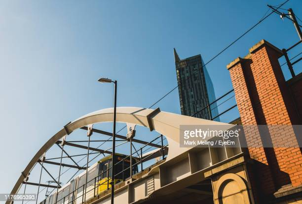 low angle view of buildings against sky - manchester england stock pictures, royalty-free photos & images