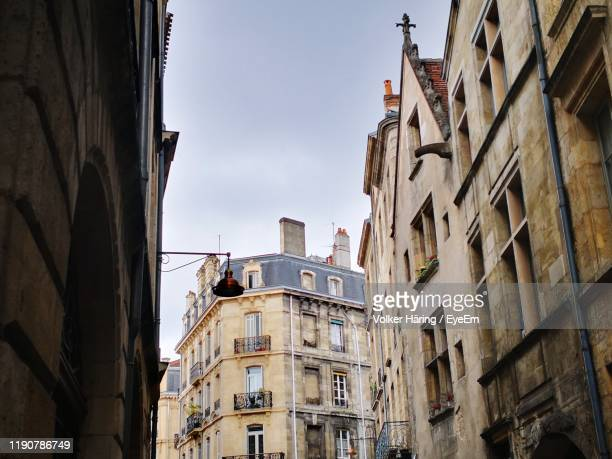 low angle view of buildings against sky - low angle view photos et images de collection