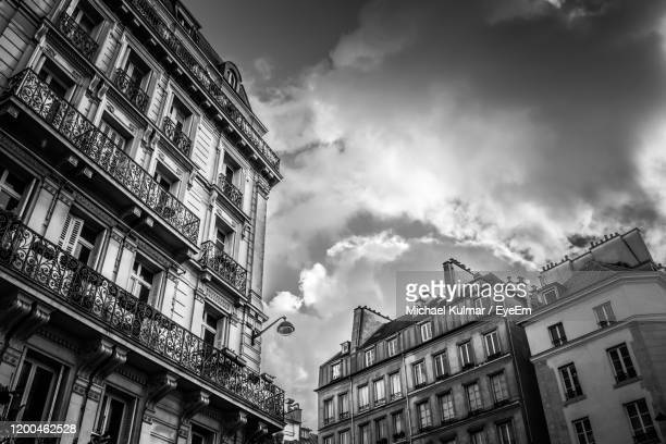 low angle view of buildings against sky - moody sky stock pictures, royalty-free photos & images