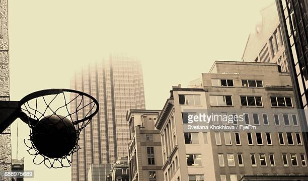 Low Angle View Of Buildings And Basketball In Hoop Net Against City Buildings
