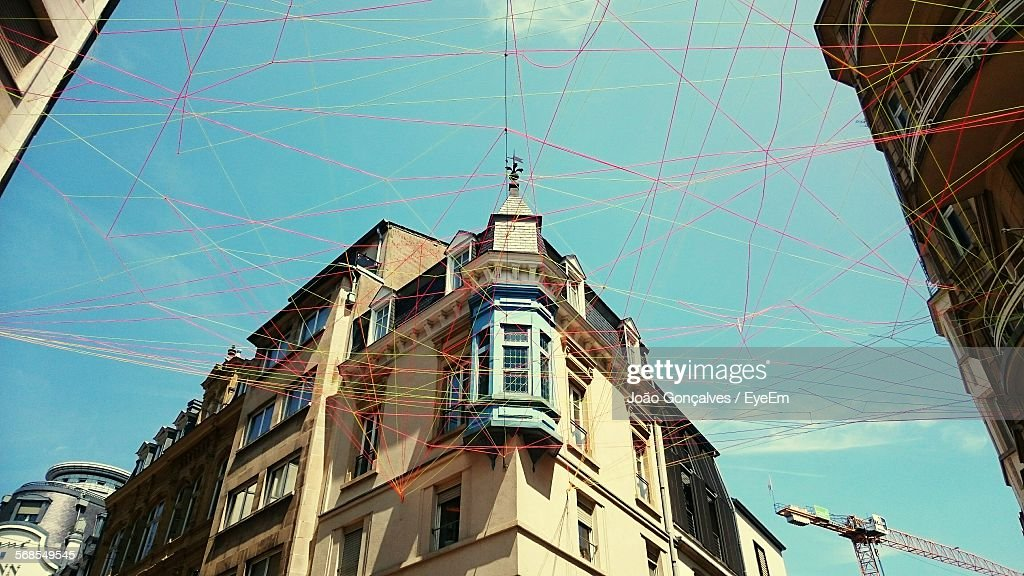 Low Angle View Of Buildings And Ropes Against Sky : Stock Photo